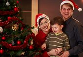 stock photo of nuclear family  - Happy parents holding small child at christmas tree boy pointing at tree - JPG