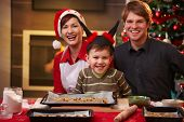 stock photo of nuclear family  - Christmas portrait of happy family of three looking at camera smiling - JPG