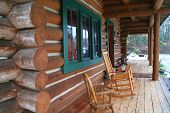 stock photo of log cabin  - a log cabin deck with rocking chairs in the forest - JPG