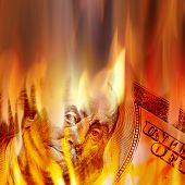 stock photo of depreciation  - Burning American money with Benjamin Franklins face appearing on fire on a one hundred dollar bill - JPG