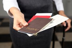 stock photo of passport cover  - Woman with suitcase holding passports and tickets close up - JPG