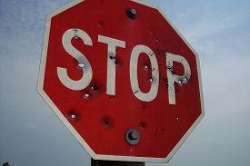 image of shotgun  - A Stop Sign obliterated with shotgun blasts - JPG
