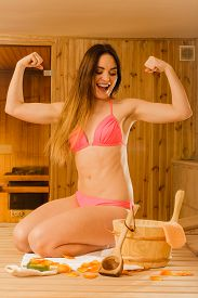 stock photo of sauna woman  - Portrait of young woman relaxing in wooden finnish sauna showing off muscles - JPG