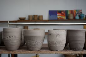 image of lineup  - lineup of homemade clay cups with variety shapes - JPG