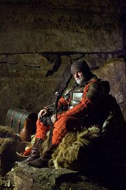pic of sword  - Old medieval King in armor with sword is sitting on furs near the camp fire - JPG