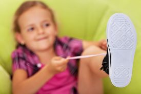 stock photo of struggle  - Little girl struggling to tie her shoes  - JPG