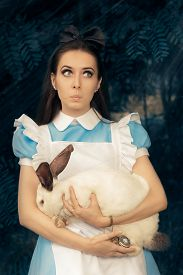 pic of bunny costume  - Portrait of a surprised girl in a blue costume holding a white bunny - JPG