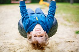 image of swing  - Funny happy preschool kid boy having fun chain swing on outdoor playground - JPG