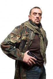 image of terrorist  - Male terrorist in a military jacket with a gun in his hand - JPG