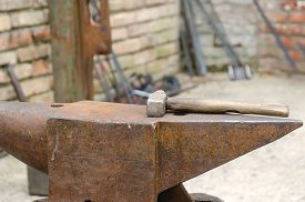 stock photo of anvil  - old anvil with iron mace in the works of the blacksmith - JPG
