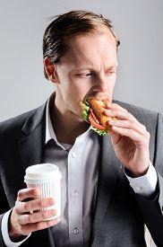 picture of takeaway  - Busy businessman eating takeaway sandwich on the go - JPG