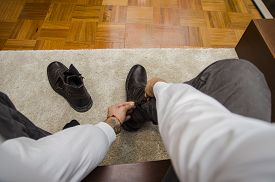 picture of pov  - Man dressing sitting on a chair bending down tying his shoe laces - JPG