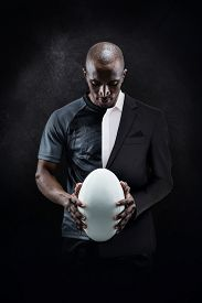 stock photo of half-dressed  - Thoughtful athlete looking at rugby ball against half a suit - JPG