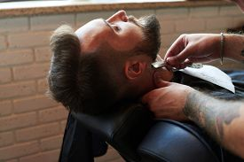 stock photo of razor  - barber shaving man with vintage straight razor in barbershop - JPG