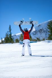 image of snowboarding  - snowboarder holding  snowboard over head  - JPG