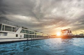 stock photo of ijs  - Ferries on the Amstel river at sunset in Amsterdam - JPG