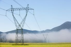 stock photo of electricity pylon  - Big electricity high voltage pylons with power lines on a green field in a foggy morning - JPG