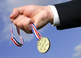 image of gold medal  - businessman grabbing gold medal against blue sky - JPG