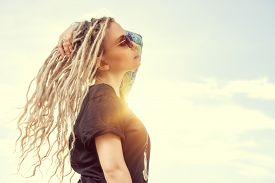 foto of dreadlock  - Modern girl with long blonde dreadlocks standing outdoor over blue sky - JPG
