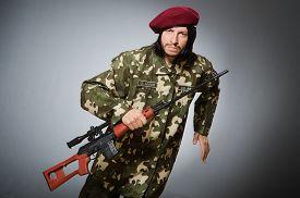 stock photo of handgun  - Soldier with handgun against gray - JPG