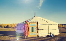stock photo of mongolian  - Mongolian Lady Standing Tent Scenic View Tranquil Concept - JPG