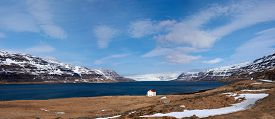 pic of iceland farm  - Quaint isolated farm house along the fjord westfjords surrounded by mountains covered in snow in Iceland - JPG
