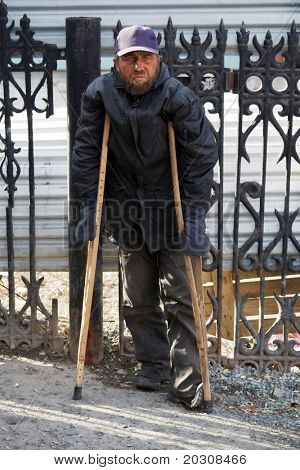 Disabled homeless man walking on crutches.