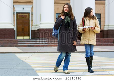 Two young students on the pedestrian crossing.