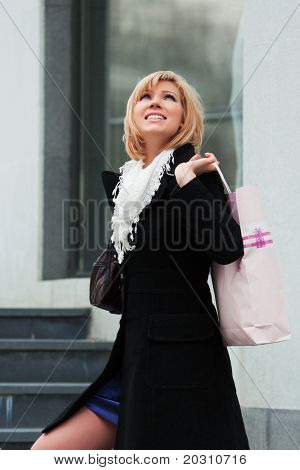 Young woman with shopping bags against of store window.