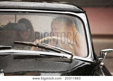 Young woman driving retro car.