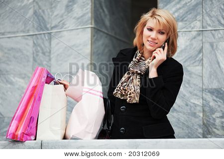 Young blond shopper on the phone.