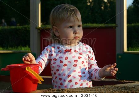 Little Girl In Sandbox Looking Away