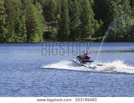 VARKAUS, FINLAND ON JULY 03. View of the surrounding by a lake where scooter, people and tourists meet on July 03, 2017 in Varkaus, Finland. Unidentified people on the jet ski. Editorial use.