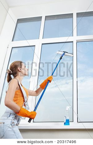 The girl in gloves washing windows mop for washing windows