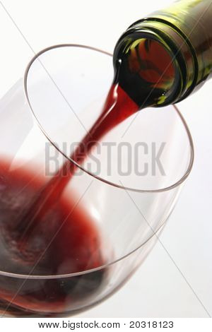 red wine being poured,bottleneck sharp,wine blurry from the movement