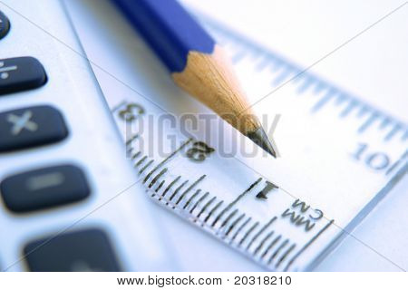 close-up of ruler,calculator,and pencil,focus on pencil-tip.blue tint