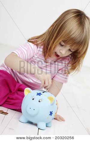 little girl putting money in her piggy bank, focus is mainly on the piggybank and hand