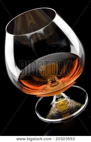 Angled view of a glass of brandy isolated on a black background