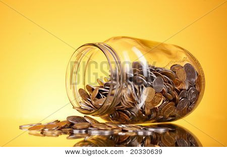 coins spilling from a money jar on yellow background. Ukrainian coins (UAH)