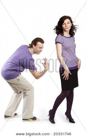 Young man going to smack with his fingers on the back of young woman just for fun.