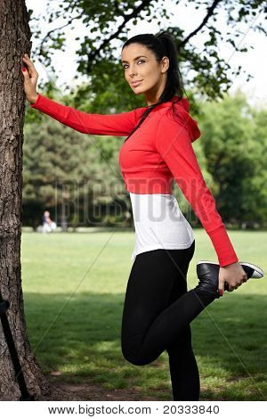 Pretty girl stretching at tree in citypark in sportswear.?