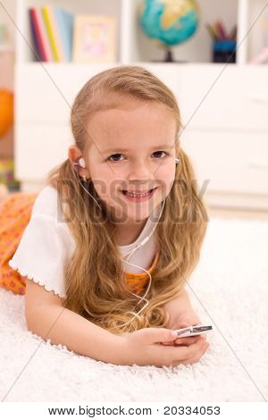 Little girl on the floor in the kids room listening to music