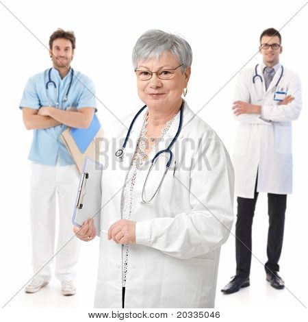 Portrait of experienced female doctor smiling, young male doctors standing behind.?