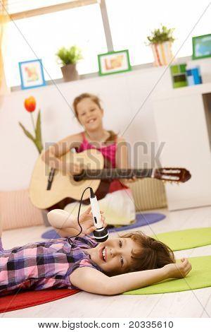 Porträt von SchülerInnen spielen andere Gitarre spielen, Musik, ein singen mit Mikrofon lächelnd.?