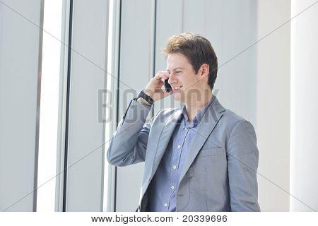 homem de negócios jovem falar pelo celular através de janela brilhante no grande hall
