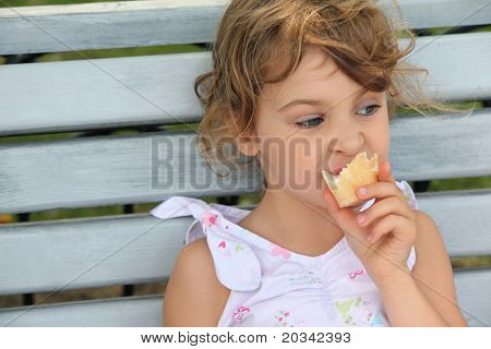 Little girl sits on bench and eats ice-cream