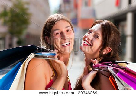 Two women being friends shopping downtown with colorful shopping bags, they are walking down a street having fun
