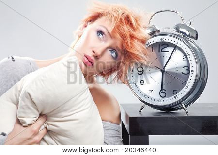 Young beauty next to alarm clock