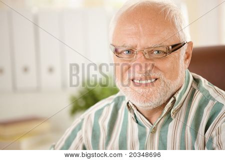 Closeup portrait of elderly man wearing glasses, smiling at camera.?