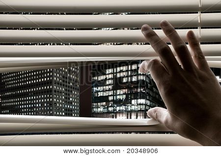 Man at office opening window blinds and seeing business towers
